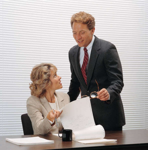 A young executive woman holds a data sheet print-out and is talking to a smiling, older man.